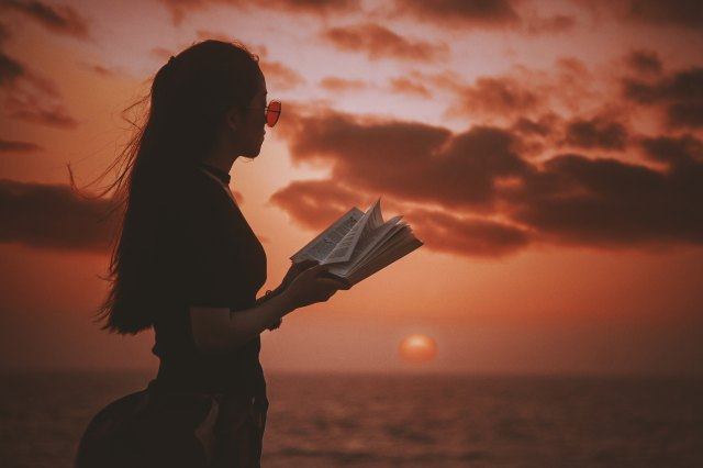 Girl reading red sunset